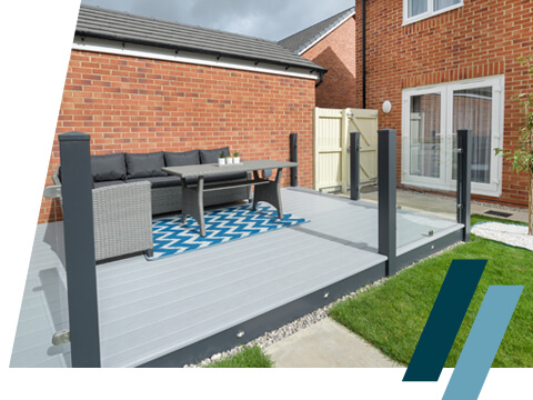 A grey decking area with glass balustrades